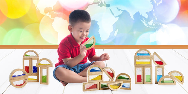 wooden stacking blocks-young boy playing with wooden building blocks that have clear windows filled with colored beads, sand or shimmering water