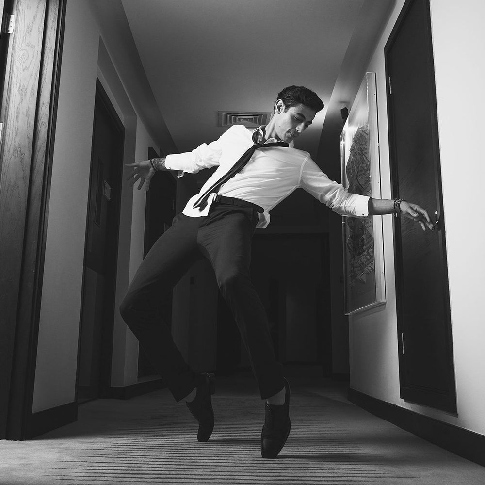 Man dressed casual breakdancing in a hotel hallway