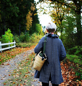 Pako bamboo bag and the Green bag in fabric on a women walking in an autumn landscape. Pako handgjord bambuväska med en grön tygväska på axeln på en kvinna i ett höstlandskap.