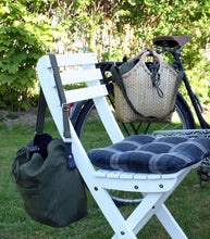 Load image into Gallery viewer, Pako bag  handmade in bamboo attached to the back of a bicycle standing in the garden, a chair with the Green bag hanging on it. Pako cykelväska som hänger på pakethållaren på en cykel som står i trädgården, en grön tygväska hänger på en stol framför.