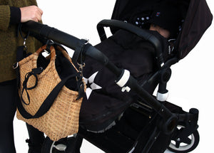 Pako strollerbag handmade in bamboo with the Black bag in fabric. Hands attaching the bag to a pram. Pako bambuväska / väska med en svart tygväska , händer sätter fast väskan på barnvagnen.