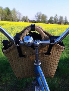 Pako bicycle bag and the Black bag attached to the handle of a bicycle with a field in the background. Pako bamboo bag and a black cloth bag, stalls are attached to the handlebars of a bicycle, a rapeseed field in the background.