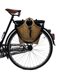 Bicycle bag handcrafted in bamboo and the black bag in fabric inside. Both attached on the back of an old black bicycle.