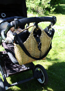 Pako stroller bag, handmade in bamboo with the Black bag in fabric attached on a parm in a park. Pako bambuväska med en svart tygväska hängandes på en svart barnvagn ståendes i parken.