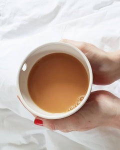 Single cup with tea in it, held by a pair of hands.