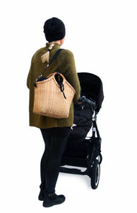A mum with Pako stroller bag, handbag handmade in bamboo and a green fabric bag. Pako bag handmade in bamboo and a green cloth bag, worn on the shoulder of a woman with a black pram