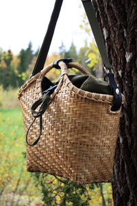 Pako bag handmade in bamboo and rattan and the Green bag in fabric, hanging in a tree. Pako bambuväska handgjord i bambu och en grön tygväska hängandes i ett träd.