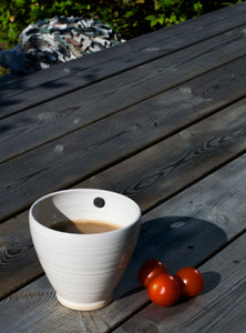 Single cup with coffee in it, tomatoes beside the cup. Single cup with coffee in, tomatoes lying next to.