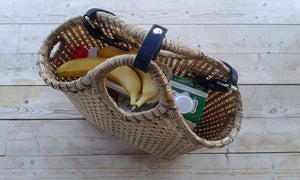 Pako bamboo bag with grocery products inside, standing on a wooden floor. Pako bamboo bag with food inside, standing on a wooden floor.