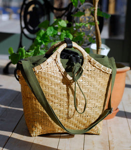 Pako bag handmade in bamboo and the Green bag in fabric standing in the sun on a wooden floor. Pako bambuväska handgjord med en grön tygväska ståendes i solen på ett trägolv.