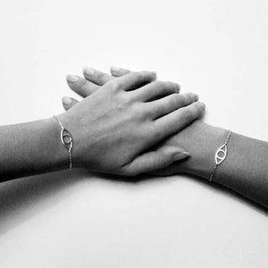 Eye bracelet and two hands wearing them. Eye silver bracelet on two hands holding each other
