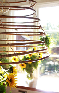 Close-up of Wish lamp in rattan, sunflowers in the background