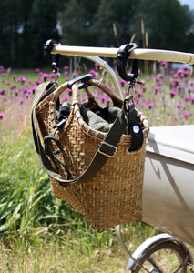 Pako stroller bag and the Green bag attach to a stroller in a summer landscape. Pako pram bag / bag handmade in bamboo attached to a pram from the 50's.