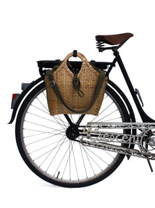Pako bicycle bag handcrafted in bamboo and the Black bag attached to the back of an old black bicycle. Pako bamboo bag handmade with a green cloth bag fastened to a package holder on a black old bicycle