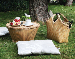 Pako bamboo table in the garden together with Pako wickerbag, bicycle bag. Pako small table in bamboo outdoors together with Pako bicycle bag in bamboo. Looks like a picnic, cake is on the table.