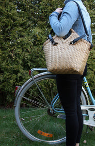 Pako bamboo bag and the Black fabric bag on a women's shoulder standing next to a bicycle. Pako bamboo bag and a black cloth bag on a woman's shoulder standing in front of a bicycle.