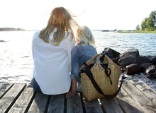 Load image into Gallery viewer, Pako bamboo bag / wicker bag handmade in bamboo with the Black bag in fabric standing behind a mum and a daugther. Pako bambuväska med en svart tygväska ståendes bakom en mamma och hennes barn