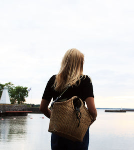 Pako bag handmade in bamboo and the Green bag in fabric worn by a model with blonde hair looking out over water. Pako bamboo bag / bag with a green cloth bag. The model carrying the bag has blonde hair and looks out over water.