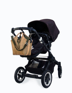 Pako stroller bag in bamboo and the Green bag, handmade in bamboo. Attached to a black stroller. Pako bag handmade in bamboo with a green cloth bag. The bag is attached to the handle of a black pram.