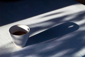 Single cup with a hole, making shadows on the table. Single cup, a cup with a hole in it that makes shadows on the table
