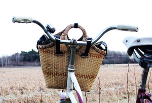Pako bicycle bag handmade in bamboo attached to a bicyle handle. Pako bamboo bag on a bicycle handle