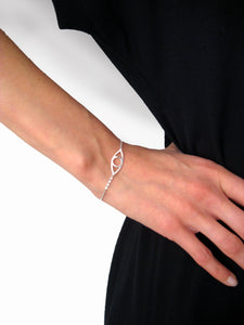 Eye bracelet 925 sterling silver handmade on a arm holding on the waist. The model is wearing a black dress. Eye armband i silver på en arm som håller på midjan. Modellen bär en svart klänning.
