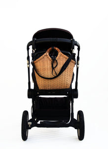 Pako stroller bag, handmade in bamboo attached on the handle of a black stroller. Pako barnvagnsväska / bambuväska handgjord hängandes på en svart barnvagn.