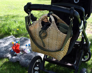 Pako bag attached to a stroller in a park, a baby blanket in the background with a toy on it. Pako pram bag / bamboo bag hanging on the handle of a black pram. A baby blanket and a red toy in the background