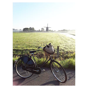 Pako bicycle bag attached to the handle of a bicycle in Haarlem outside Amsterdam, behind is green field with an old windmill. Pako bicycle bag on the bicycle handlebar on an old bicycle with a green field and an old windmill in the background.