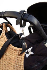 Pako bag hanging on a stroller with leather straps. The Pako bag hangs on the pram with leather straps.