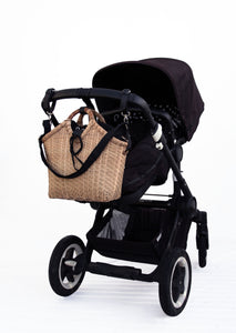Pako stroller bag in bamboo with the Black bag hanging on a black pram. Pako bambuväska handgjord med en svart tygväska hängandes på en svart barnvagn