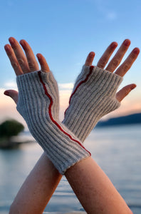 Photo advertising knitting pattern for fingerless mitts. Photo shows two hands extended in the air with a river in the backdrop. The mitts are made with grey alpaca and feature brioche stitches and a red seam.