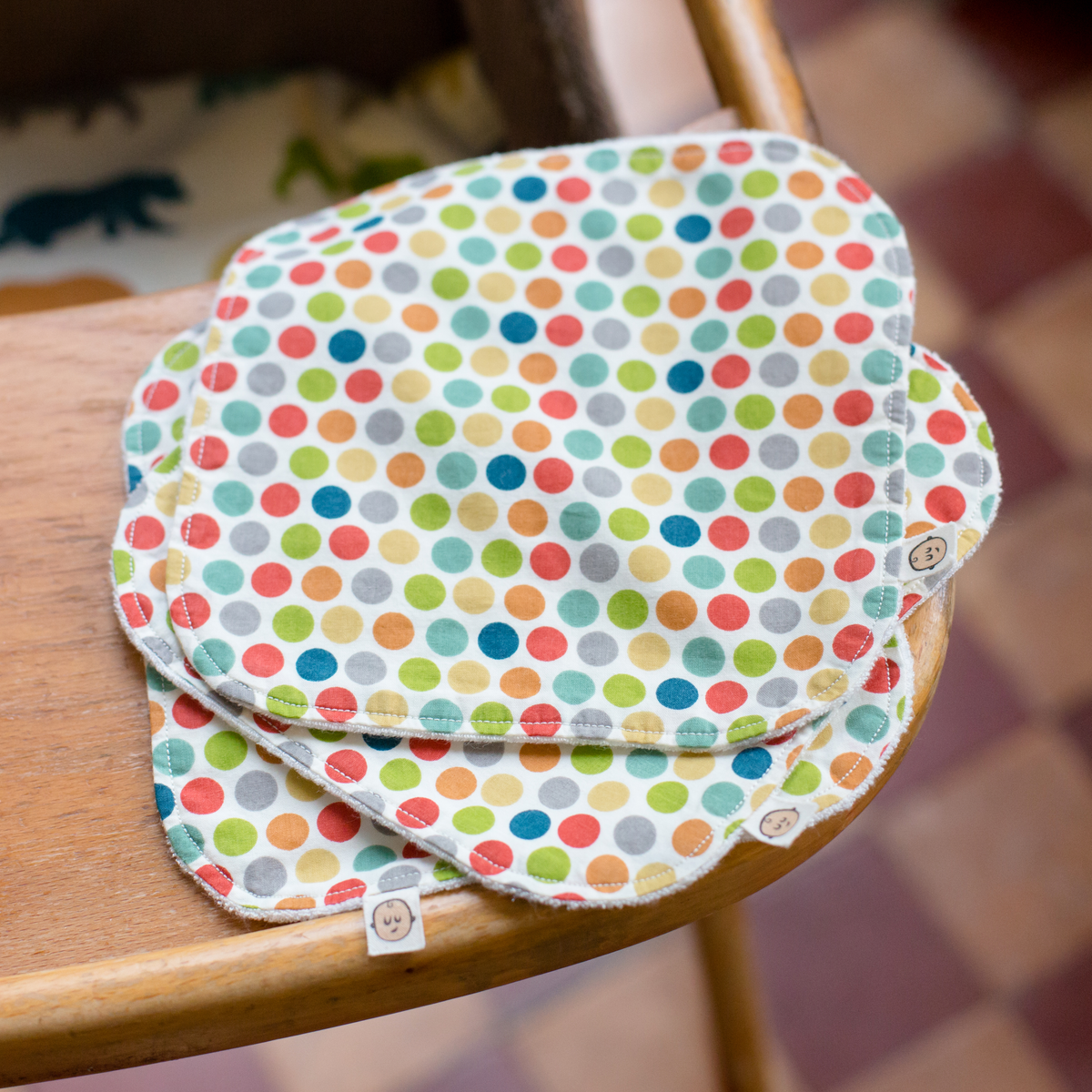 A set of three organic Poco Bambino wash cloths / wipes in a rainbow dots design