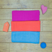 Load image into Gallery viewer, Three Poco Bambino organic muslin cloths in pink, orange and blue. Pictured with three wooden toys
