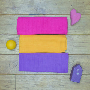 Three Poco Bambino organic muslin cloths in pink, yellow and purple. Pictured with three wooden toys