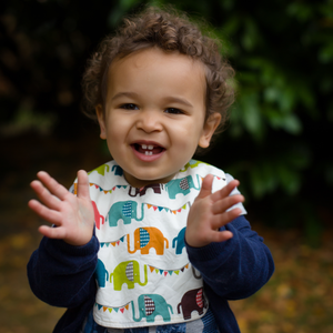 A male toddler clapping his hands and wearing a Poco Bambino organic bib in a rainbow elephant parade print