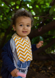 A male toddler wearing a Poco Bambino organic bib in an orange chevron print