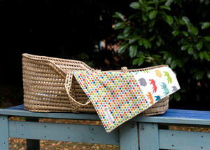 A Poco Bambino organic pram blanket in dottie and bear hike prints laid over a moses basket on a bench outside