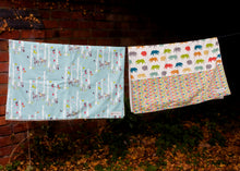 Load image into Gallery viewer, Two organic Poco Bambino blankets hanging on a washing line. One is a forest print, the other is rainbow dots and bears