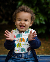 Load image into Gallery viewer, A male toddler clapping his hands and wearing a Poco Bambino organic bib in a rainbow elephant parade print