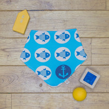 Load image into Gallery viewer, An organic Poco Bambino dribble bib. The print is blue with a fish and anchors sailors design.