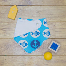 Load image into Gallery viewer, An organic Poco Bambino dribble bib. The print is blue with a fish and anchors sailors design. One corner is folded up to show the organic cotton and bamboo terry reverse