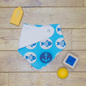 An organic Poco Bambino dribble bib. The print is blue with a fish and anchors sailors design. One corner is folded up to show the organic cotton and bamboo terry reverse