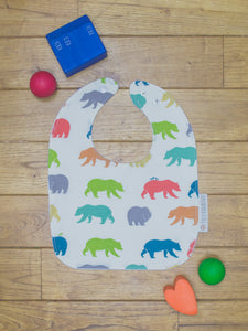 An organic Poco Bambino bib. The print is rainbow bear hike design.