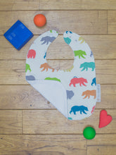 Load image into Gallery viewer, An organic Poco Bambino bib. The print is rainbow bear hike design. One corner is folded up to show the organic cotton and bamboo terry reverse