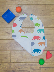An organic Poco Bambino bib. The print is rainbow bear hike design. One corner is folded up to show the organic cotton and bamboo terry reverse