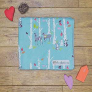 An organic Poco Bambino blanket. The print is turquoise with a forest design. One corner is folded up to show the organic cotton and bamboo fleece reverse