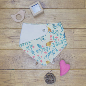 An organic Poco Bambino dribble bib. The print is a birds and branches design. One corner is folded up to show the organic cotton and bamboo terry reverse