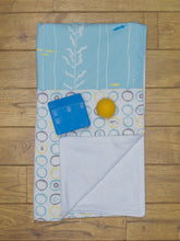 Load image into Gallery viewer, An organic Poco Bambino blanket. The print is blue, yellow and grey with a sea creatures design. One corner is folded up to show the organic cotton and bamboo fleece reverse