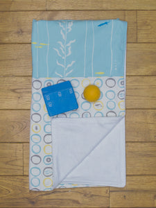 An organic Poco Bambino blanket. The print is blue, yellow and grey with a sea creatures design. One corner is folded up to show the organic cotton and bamboo fleece reverse